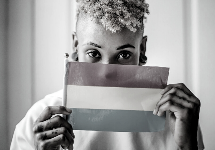 Person looking at the camera holding a Trans flag