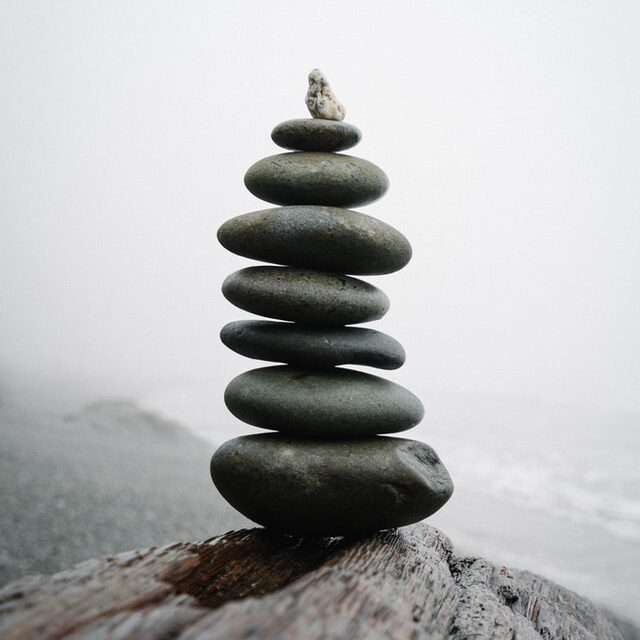 Pile of 8 round, smooth stones piled on top of each other, from big to small, with ocean backdrop