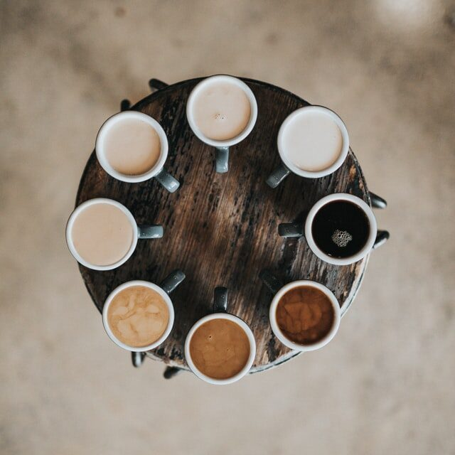 Top view of round wooden table with mugs filled with coffee of different shades