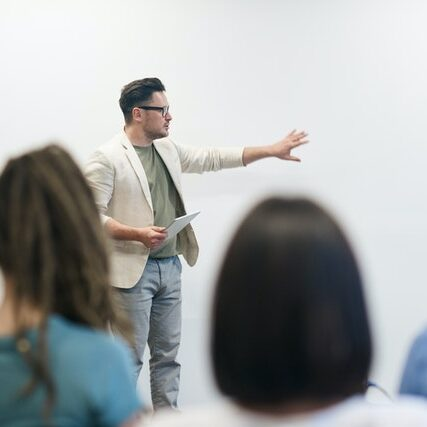 Professor in action teaching class with back of heads of students blurred out