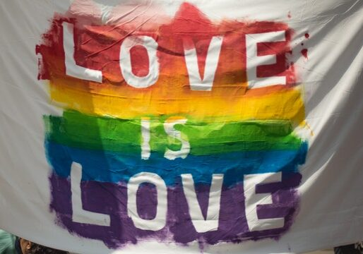 """Flag with a display of Pride colours and the words """"Love is Love"""""""